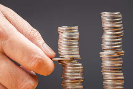 Hand try to pull out a coin from the heap, risk to lose a balance, commission or taxes payment concept