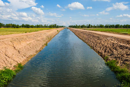 Unfinished irrigation canal through the rice field, infrastructure during construction and development in countryside of Thailand
