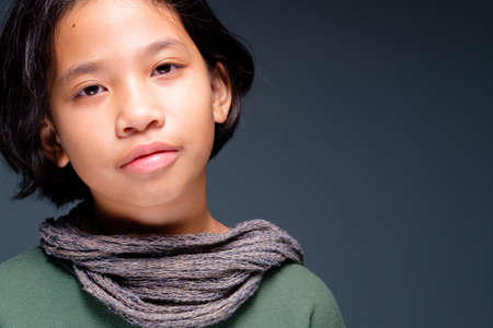 Head shot portrait of ten years old girl wearing green shirt and scarf in studio 写真素材