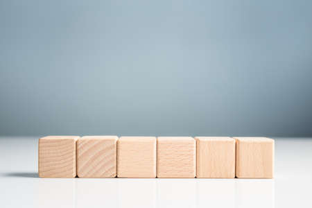 Wood blocks in a row on green wall background, element for insert icon or text with copy space Stock Photo