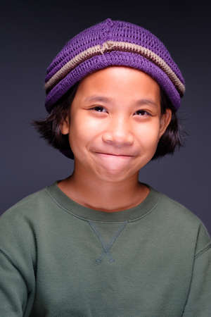 Portrait of ten years old child wearing green shirt and wool hat, and smiling at the camera