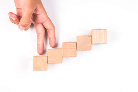 Closeup human's hand gesture finger walking and step up on the wood cubes arranged as staircase on white background