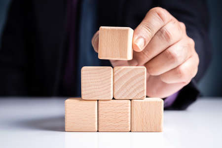 Closeup businessman stack the wood block for a pyramid stair shape, business growth concept 写真素材