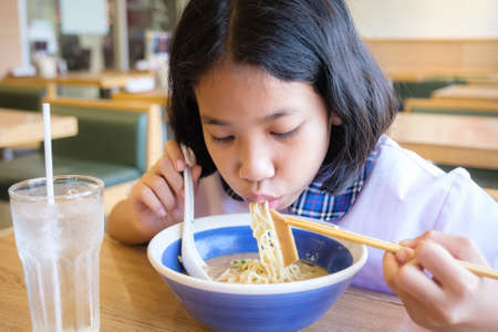 Thai student eating Japanese noodle soup after school in the restaurant that has few customers