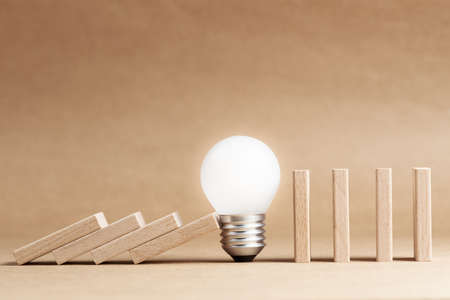 Glowing light bulb block the falling domino in a row, problem and solution, creative idea to stop the collapse 写真素材
