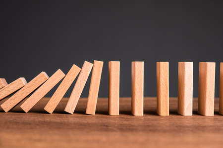 Closeup wooden domino on the table starting to fall down and affect to the others in a row