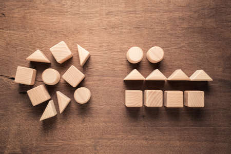 Confused geometry shape of wood blocks on the left rearrange in the same category on the right, category concept 写真素材