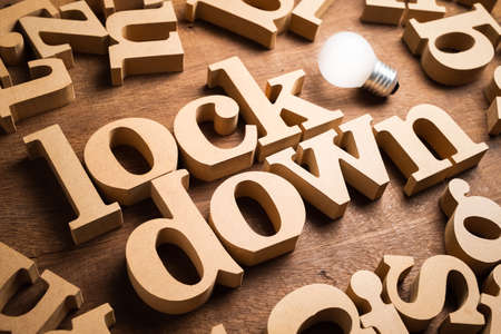 LOCKDOWN wood word in scattered alphabets with glowing light bulb as symbol of tips or idea for work and activities during covid-19 pandemic 写真素材