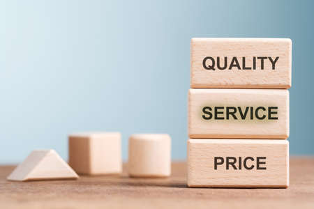 Quality, Service and Price text on stack wood blocks, low price and high quality of service concept