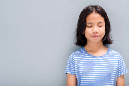 Little Thai girl in casual cloths standing and close her eyes to meditating and be calm