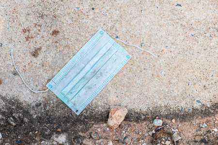 Closeup a dirty and torn surgical face mask become the garbage leaving on the ground along the street, covid-19 and environment, pandemic and ending