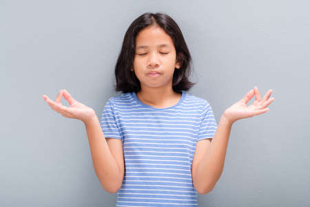 Ten years old Thai girl in casual cloths standing at the wall, gesture yoga hands and close her eyes to meditating