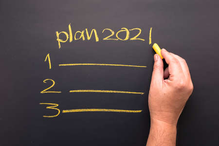 Hand writing topic of 2021 plan on chalkboard, goal setting and priority  in coming year