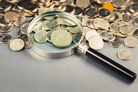 Magnifying glass on the pile of money coins on the table, financial status, economic analysis 写真素材
