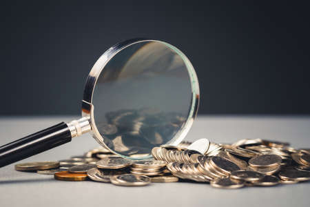 Magnifying glass on the pile of money coins on the table 写真素材