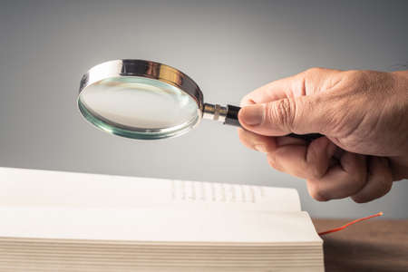 Closeup hand hold the magnifying glass over the opened pocket book on the table