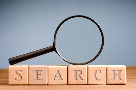 Arranged wood block and magnifying glass with text SEARCH, searching sign concept Standard-Bild