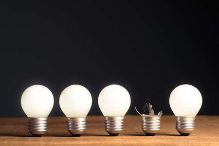 Many glowing light bulbs in a row but only one is lost and break, unsuccessful or useless idea, success and failure concept 版權商用圖片
