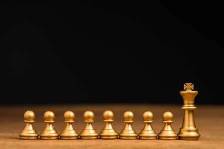 Golden king chess and row of pawns on black background