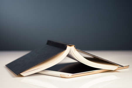 Opened book placed upside down above the digital tablet, create content for online business