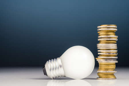 Heap of money coins with light bulb, concept of tips to make money or start business, creativity and make idea happen