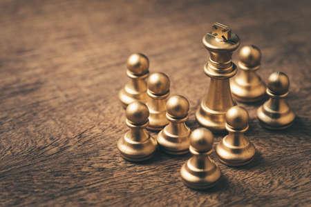 Closeup king chess with many pawns around, leadership and teamwork concept 版權商用圖片
