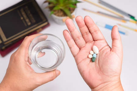 Closeup hands holding pills and glass of water, prepare to take medicine over the desk