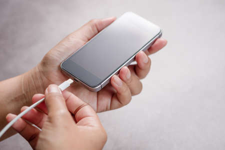 Closeup hand going to charge battery on mobile phone 版權商用圖片