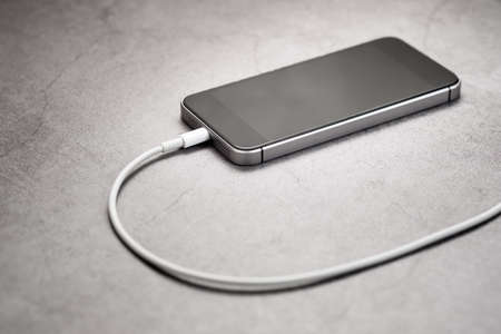 Closeup mobile phone in charging on the table 版權商用圖片