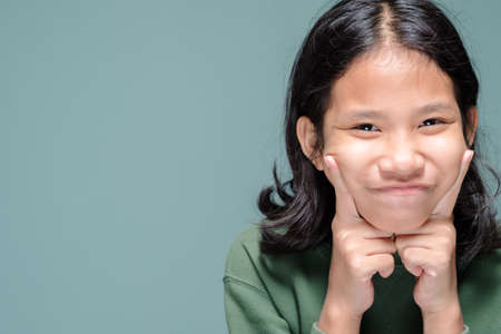 Ten years old girl touch her cheeks with two index fingers and smile with a little bit shy