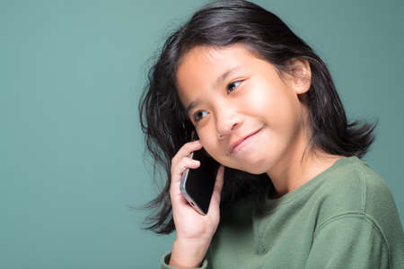 Ten years old girl is talking on mobile phone, thai child in studio on green wall background