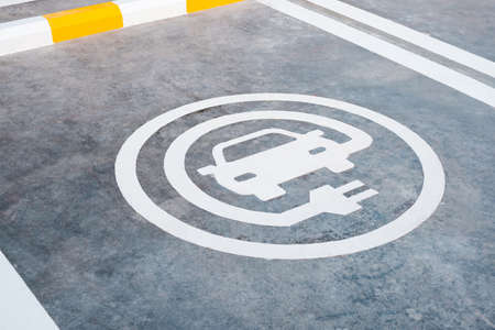 EV or electric car charging sign painted on the ground of parking lot in gas station in Thailand