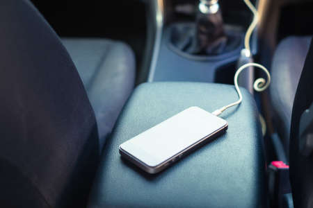 Closeup smartphone placed on the armrest in the car and charging by power socket from the front console, view from the back seat