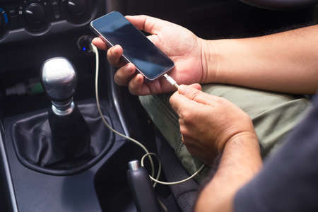 Closeup hands holding smartphone and going to charge battery by power supply socket in private car