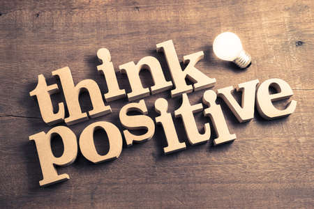 Think Positive : block wood word arranged on wood background with glowing light bulb