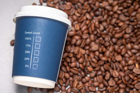 Sweet Level text with percentage and check box printed on portable cup with pile of coffee beans, concept for amount of sugar, diet and diabetes about coffee 版權商用圖片