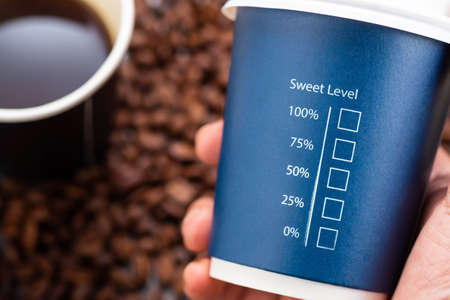 Hand holding cup and show sweet Level text and percentage check box with black coffee and pile of coffee beans on background, concept for amount of sugar, diet and diabetes