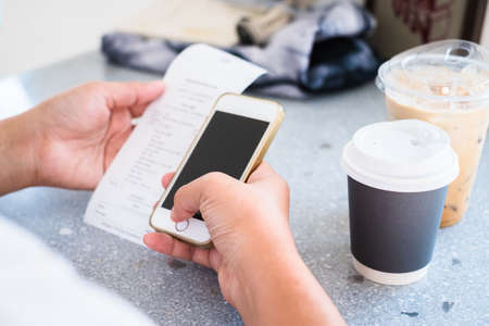 Woman use smart phone to calculate the bill or check the price of drinks with coffee on the table in the cafe, online payment concept Standard-Bild