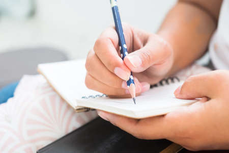 Closeup woman sitting in the room and take a note on small notepad with pencil 版權商用圖片