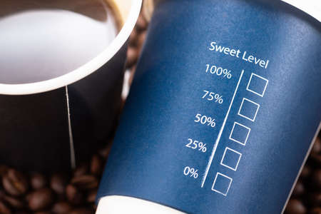Sweet Level text with percentage and check box printed on portable cup with cup of black coffee, concept for amount of sugar, diet and diabetes