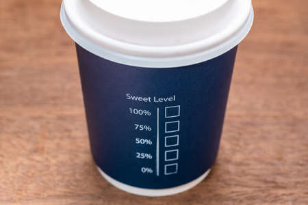 Portable coffee cup with text : Sweet Level and percentage check box, on wood table, concept for amount of sugar, diet and diabetes