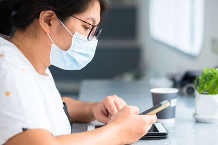 Closeup woman wearing hygienic face mask use smartphone in the cafe, people lifestyle during covid-19 pandemic 版權商用圖片