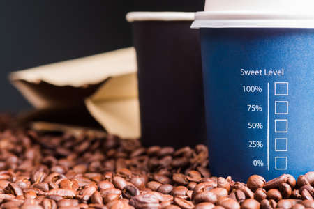 Portable coffee cups with text : Sweet Level and percentage check box, on pile of coffee beans, concept for amount of sugar, diet and diabetes about coffee