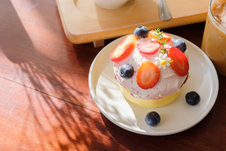 Wild berry cream cheese cake with part of drinks on wood table