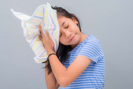 Ten years old girl drying her wet hair with towel after bath, isolated on light green wall