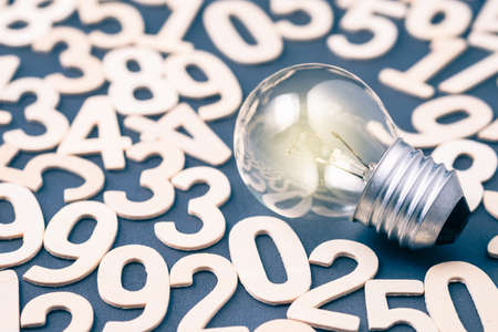 Glowing light bulb on many messy numbers, calculation and mathematics concept