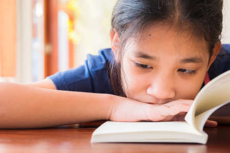 Closeup face of child girl place the chin down on the hand, reading closely to follow the story in the book 版權商用圖片