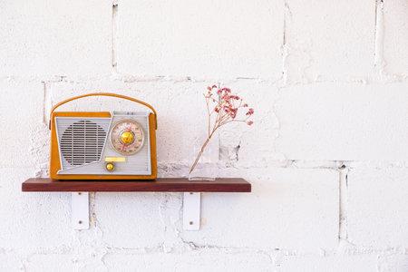 Old vintage radio and dry flower vase decorated on wood shelf on the white brick wall 版權商用圖片