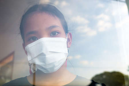 Ten years old girl with hygienic face mask standing at the window inside the house and looking out to the camera 版權商用圖片