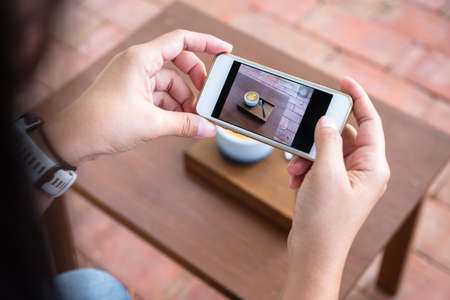 Closeup woman holding mobile phone to take a photo of cappuccino coffee on the table
